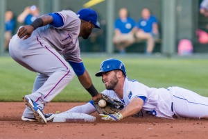KANSAS CITY, MO - JUNE 05: Mike Moustakas #8 of the Kansas City Royals attempts to avoid the tag at second base from Hanser Alberto #68 of the Texas Rangers in the first inning at Kauffman Stadium on June 5, 2015 in Kansas City, Missouri. Moustakas was called safe initially but after review was called out. (Photo by Kyle Rivas/Getty Images)