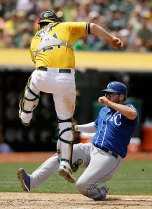 Kansas City Royals' Mike Moustakas, right, scores beneath Oakland Athletics catcher Stephen Vogt in the sixth inning of a baseball game Sunday, June 28, 2015, in Oakland, Calif. (AP Photo/Ben Margot)