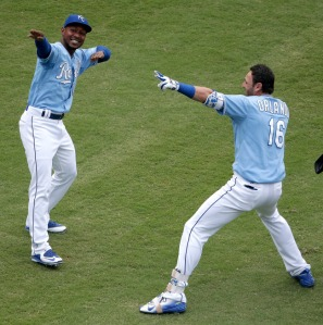 Kansas City Royals' Jarrod Dyson and Paulo Orlando (16) celebrate after Orlando hit a walk-off grand slam during the ninth inning of the first game in a baseball doubleheader against the Tampa Bay Rays Tuesday, July 7, 2015, in Kansas City, Mo. The Royals won 9-5. (AP Photo/Charlie Riedel)