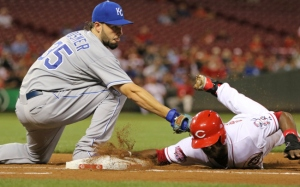 Cincinnati Reds' Jason Bourgeois (30) dives safely back to first base as Kansas City Royals first baseman Eric Hosmer (35) applies the tag on a pick-off attempt during the third inning of a baseball game, Wednesday, Aug. 19, 2015, in Cincinnati. (AP Photo/Gary Landers)