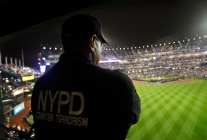 New York Police Department Counter Terrorism Agent Sgt. Kevin Mikowski watches from a camera platform during a 9/11 remembrance ceremony before the New York Mets baseball game against the Chicago Cubs at Citi Field, Sunday, Sept. 11, 2011, in New York. (AP Photo/Kathy Willens)