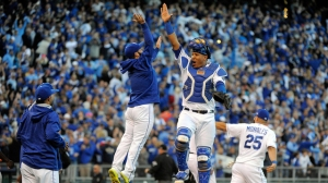 KANSAS CITY, MO - OCTOBER 09:  Salvador Perez #13 and Tim Collins of the Kansas City Royals celebrate after defeating the Houston Astros in game two of the American League Division Series at Kauffman Stadium on October 9, 2015 in Kansas City, Missouri.  The Royals defeated the Astros with a score of 5 to 4.  (Photo by Ed Zurga/Getty Images)