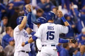 KANSAS CITY, MO - OCTOBER 28: Alcides Escobar #2 of the Kansas City Royals and Alex Rios #15 of the Kansas City Royals celebrate with Kendrys Morales #25 of the Kansas City Royals after scoring runs in the fifth inning against the New York Mets in Game Two of the 2015 World Series at Kauffman Stadium on October 28, 2015 in Kansas City, Missouri. (Photo by Sean M. Haffey/Getty Images)